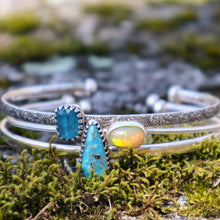 Load image into Gallery viewer, A set of three stacking bracelets each with a different stone shown in some green moss. There is one bracelet with a blue apatite stone, one bracelet with a flashy oval opal, and one bracelet with a tear drop shaped blue turquoise stone