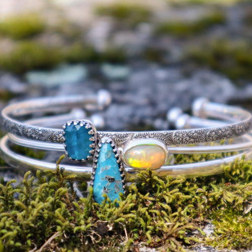 A set of three stacking bracelets each with a different stone shown in some green moss. There is one bracelet with a blue apatite stone, one bracelet with a flashy oval opal, and one bracelet with a tear drop shaped blue turquoise stone