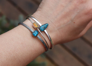 A set of three stacking bracelets shown being worn on a wrist