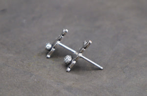 A side view of two earrings that are rabbits made by The Striped Cat Metalworks.
