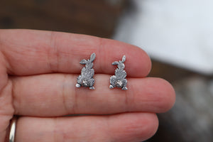 A pair of rabbit earrings shown in a hand for size reference.