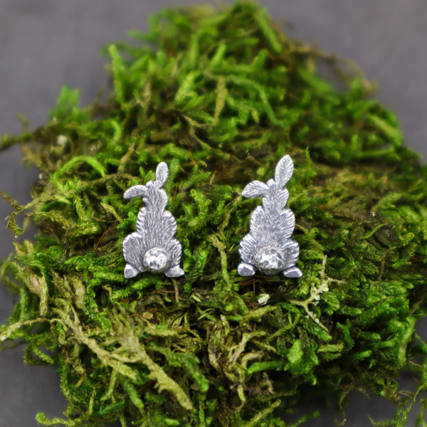 sterling silver rabbit bum earrings shown on a fluffy piece of bright green moss made by The Striped Cat Metalworks.