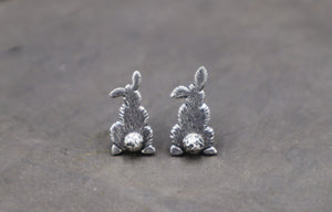Silver handmade bunny bum stud earrings shown on a piece of dark grey slate.