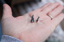 Load image into Gallery viewer, A paid of handmade sterling silver rabbit earrings show in a hand at a side angle for size reference.