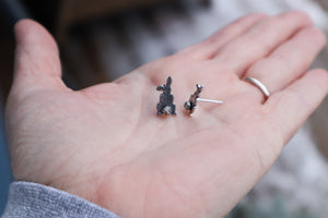 A paid of handmade sterling silver rabbit earrings show in a hand at a side angle for size reference.