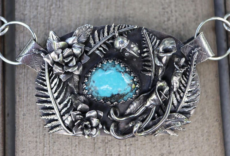 A sterling silver flower garden pendant with a bright blue turquoise and pyrite stone in the center. There are calla lilies, roses, ferns, and a tiny little ladybug all made from silver on the pendant.