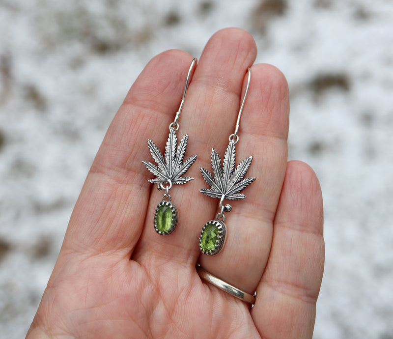 A hand is shown holding a handmade pair of sterling silver cannabis leaf earrings with green peridot stones.