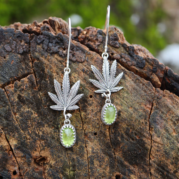 Sterling silver cannabis leaf earrings with genuine grass green rose cut peridot stones dangle below them. They are shown on a piece of dark brown wood.