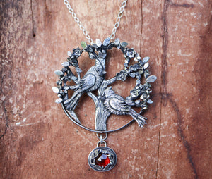 A handmade northern cardinal sterling silver necklace shown on a piece of dark red wood. The cardinals are sitting in a silver tree with lots of leaves around them. At the bottom of the necklace dangles a dark red garnet stone that is rose cut so that it catches the light and shines.