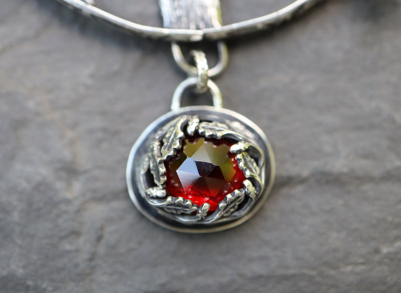 A close up shot of the red garnet rose cut stone at the bottom of the pendant. It is shown on a dark grey stone.