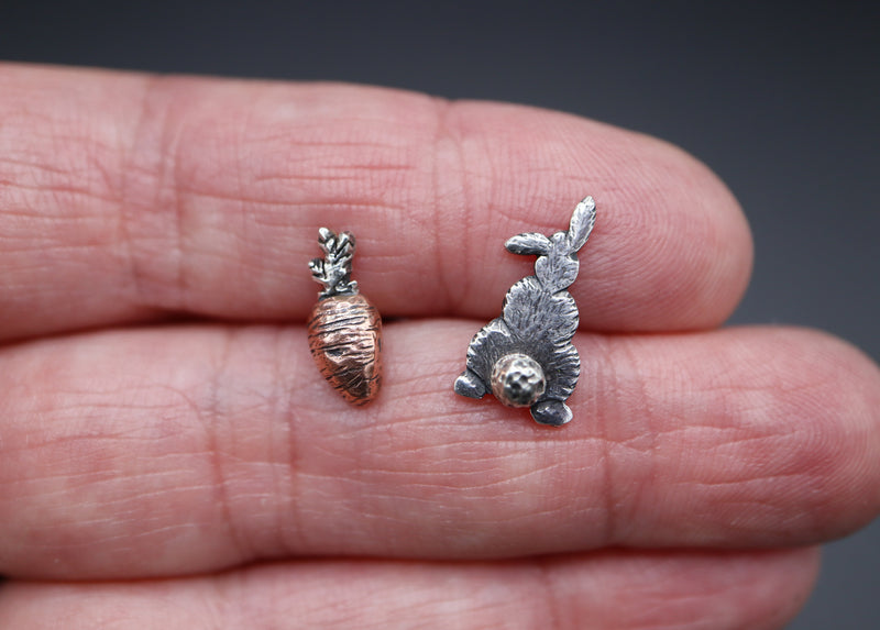 A hand is holding a pair of mismatched stud earrings. One earring is a sterling silver bunny back with a fluffy tail. The other earring is a carved copper fat carrot with a sterling silver top.