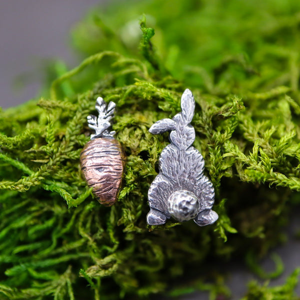 A handmade pair of stud earrings that are mismatched. One earring is an etched silver bunny back with his fluffy tail showing. The other earrings is a hand carved copper fat carrot with a sterling silver top. They bunny is about 1/2 inch tall. They are shown on some bright green moss.