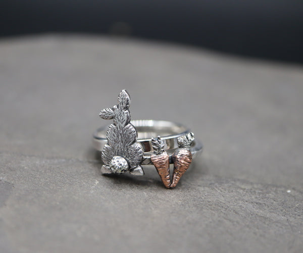A rabbit ring and a copper carrot ring stacking set. They are shown on a dark grey piece of slate.