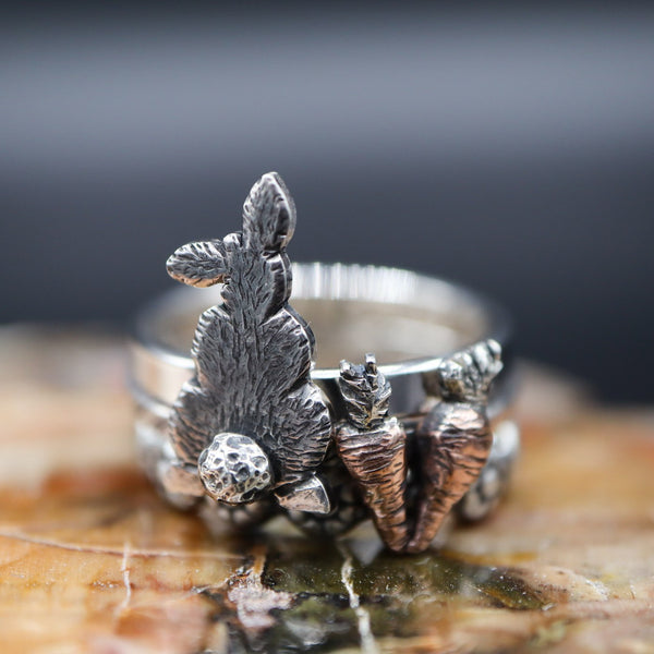 A set of three stacking rings featuring a rabbit's back with a fluffy tail, a set of two tiny hand carved copper and silver carrots, and a flower head band. They are shown on a piece of light brown stone.