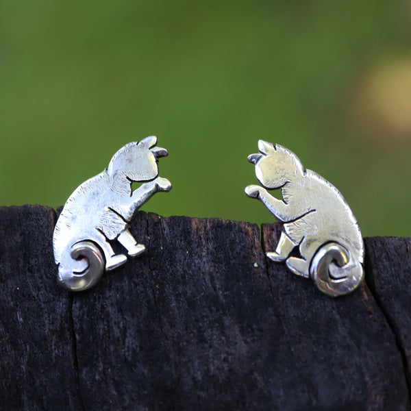Small sterling silver stud earrings of cut out cats cleaning their front paws pictured on a piece of wood made by The Striped Cat Metalworks.