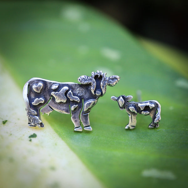 A little cow and calf handmade sterling silver earring studs. The momma cow is a bit larger than the calf earring. They are shown on a green and white plant leaf.