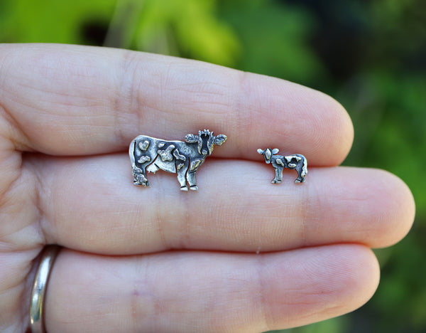 A hand is holding a pair of handmade sterling silver cow and calf earring studs to show size. The earrings are bout 1/2 an inch and 1/4 of an inch each.