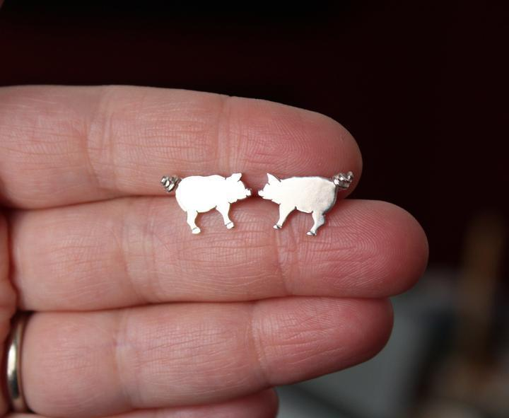 A hand is shown holding a pair of handmade sterling silver pig earrings with tiny curly tails.