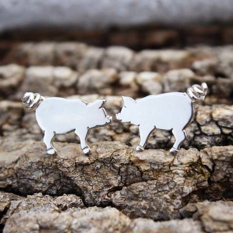A pair of handmade sterling silver pig earrings are shown on a piece of tree bark.