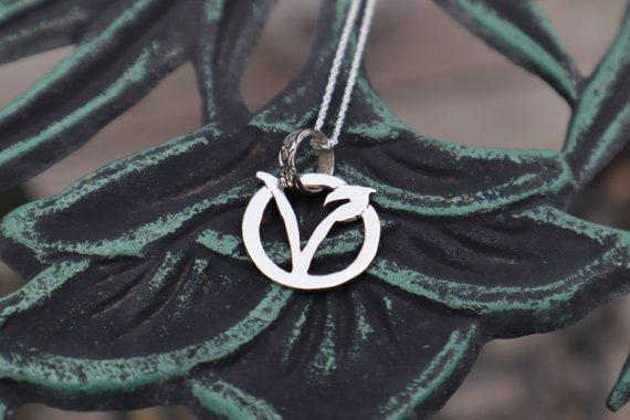 A circle v necklace is shown on a dark green metal table.