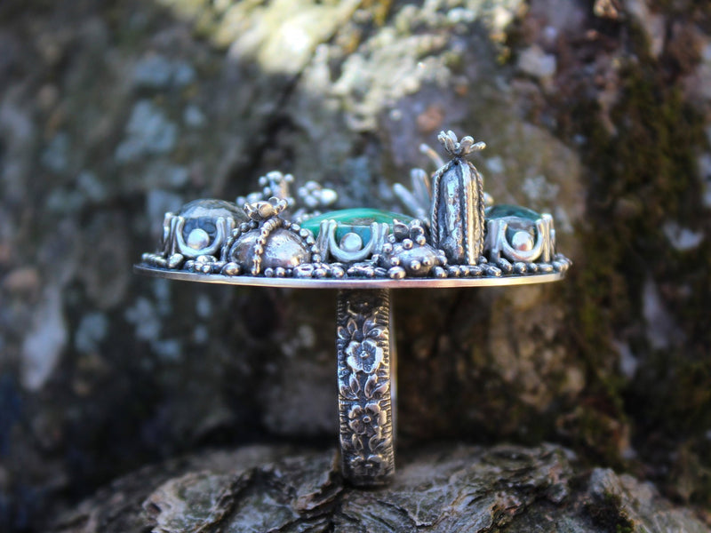 The side view of the damele turquoise ring showing several of the cactus on the top of the ring. You can also see the floral band of the ring.