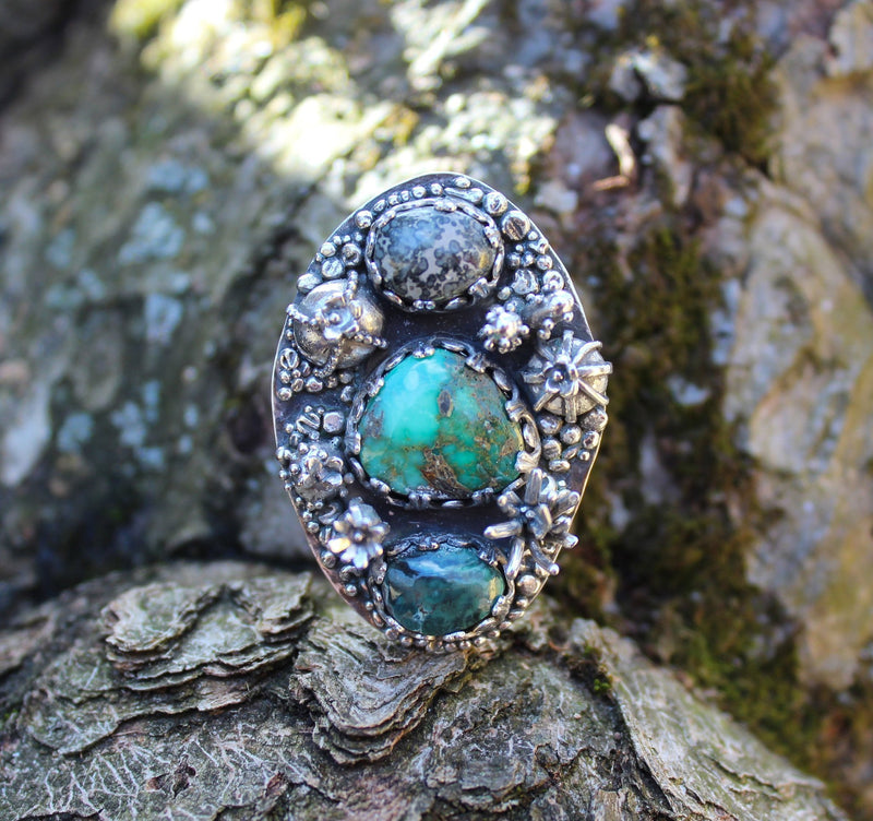 A front view of the damele turquoise ring showing the three stones and all the cactus. The ring is shown on a piece of tree bark.