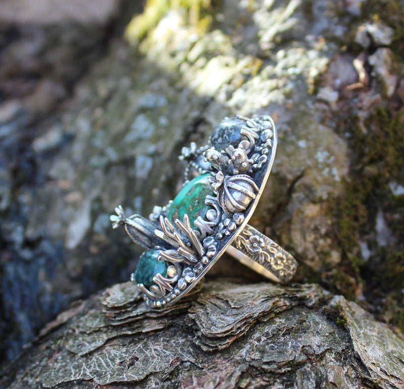 A side view of the damele turquoise ring showing several of the sterling silver hand carved cactus.