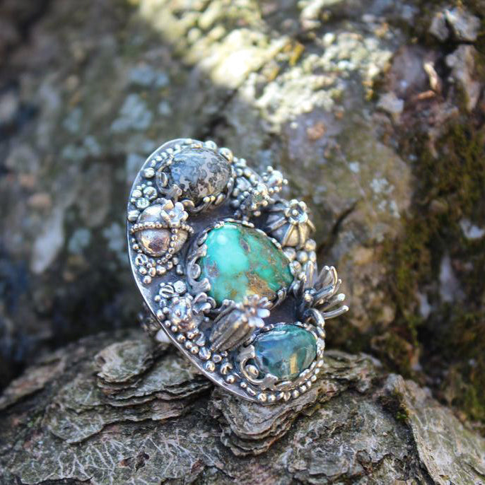 A damele turquoise ring surrounded by tiny sterling silver hand carved cactus to make the ring look like a garden. he ring has three stones and many little plants around them. The ring is shown on a piece of tree bark.