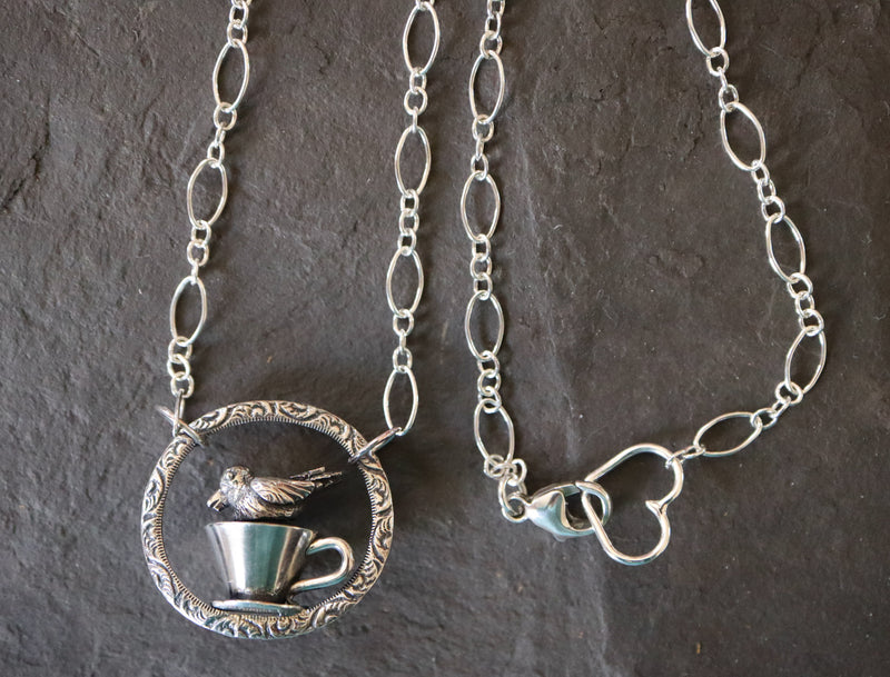 A sterling silver handmade tiny duckling in a teacup necklace shown on a piece of dark grey slate.