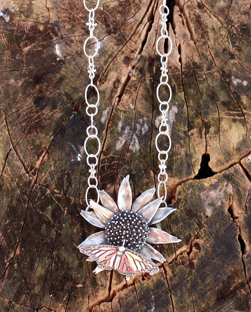 An outside photo of the monarch and echinacea necklace shown on a tree stump.