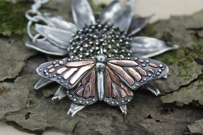 An echinacea flower handmade from sterling silver with a copper and silver monarch butterfly pendant. The necklace is shown on a piece of wood and bark.