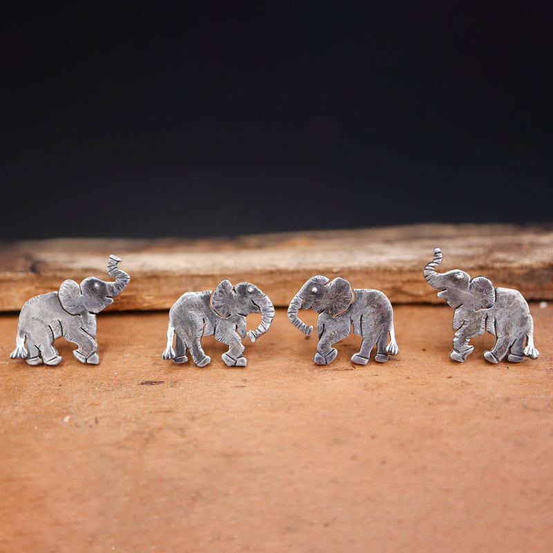 Four pairs of handmade sterling silver elephant earrings. Two pairs have their trunks up, two pairs have their trunks down. They are all shown in a piece of light brown wood.