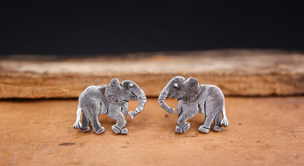 A pair of sterling silver handmade elephant earring studs that are about 1/2 inch tall and are shown on a light brown piece of wood.