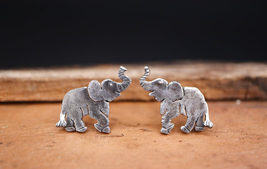 A pair of handmade sterling silver elephant earring studs that are about 1/2 inch tall and have their trunks up in the air.