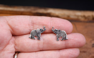 A hand is shown holding a pair of 1/2 inch tall elephant earring studs to show the size.