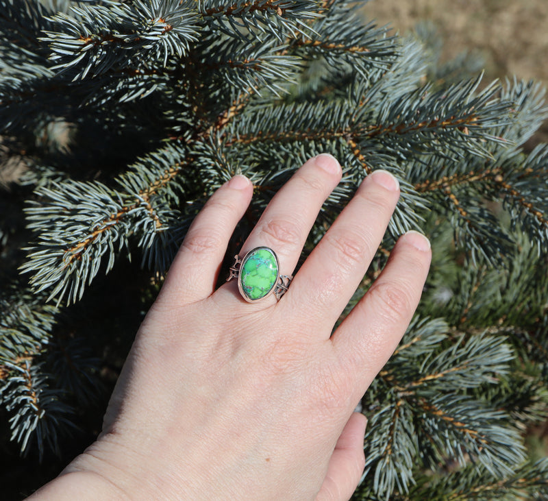 A hand is shown wearing the size 10 faustite turquoise stone in front of an evergreen tree.
