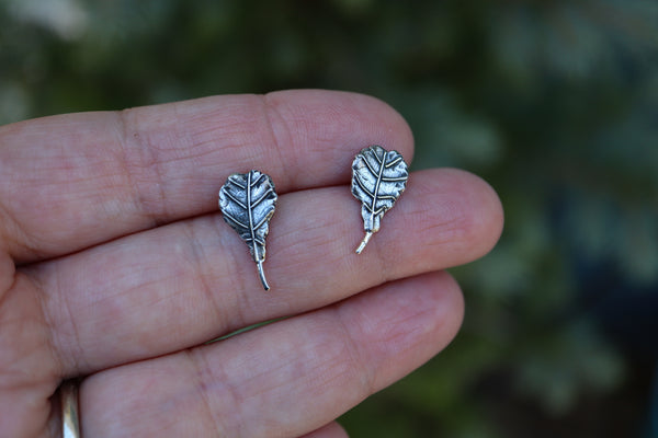 A hand holding a pair of handmade sterling silver fiddle leaf fig earrings to show size. They are about 1/2 inch tall.