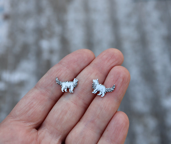 A hand is holding a pair of sterling silver fluffy cat earrings that are about 1/2 inch tall.