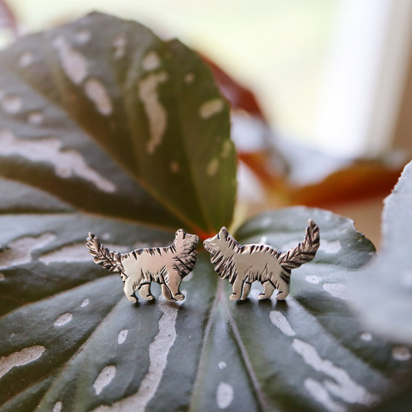 Hand etched sterling silver fluffy cat earrings are about 1/2 inch tall and show on top of a spotty plant leaf.