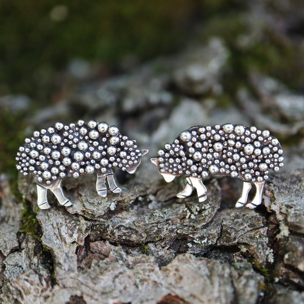 sterling silver handmade sheep earrings with bright silver balls to make them look fluffy. They are about .75 inches wide and shown on a piece of apple tree bark.