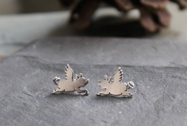 Another view of the sterling silver flying pig studs. They are shown on a piece of light grey stone.