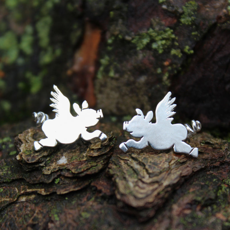 Handmade sterling silver flying pig earrings. The pigs have cute outstretched legs and a little curly tail behind them. They are shown on a piece of dark tree bark.