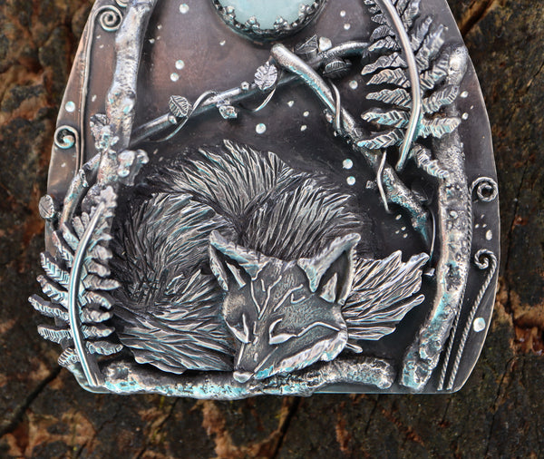 A close up of the multi layered sterling silver fox kit necklace. He is surrounded by silver twigs, vines, and ferns.