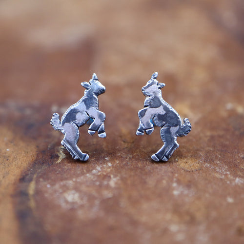Playful goat kid earrings made from sterling silver and they are shown on a dark brown piece of wood. The goats are silver colored with some darker spots so that they look like they are spotted black and white.