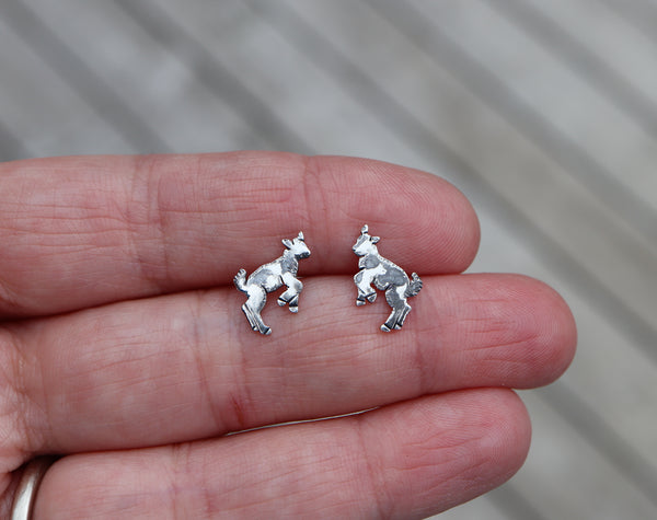Small silver goat earrings that are kicking up into the air being silly. They have darkened spots on them so that they look black and white. A hand is shown holding them for size reference.