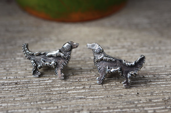Small sterling silver stud golden retriever earrings are shown on a piece of dark grey wood.