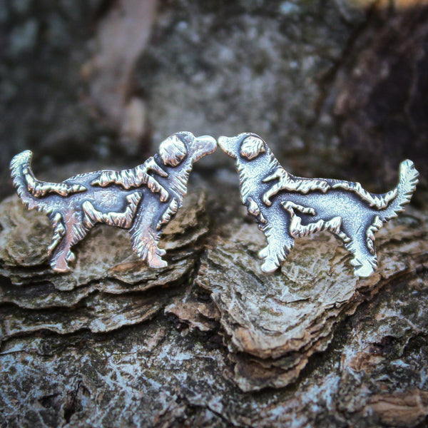 Sterling silver golden retriever stud earrings are shown on a dark grey piece of tree bark.