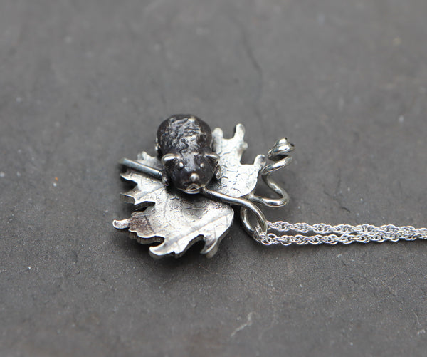 The face of the little silver guinea pig. He is attached to a silver maple leaf and shown on a dark grey piece of stone.