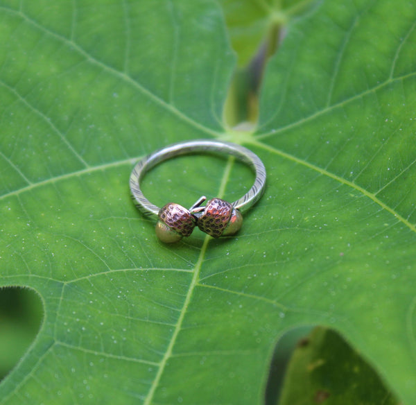 Handmade coper carved acorn ring with a striped pattern sterling silver band. The ring is shown on a light green plant leaf.