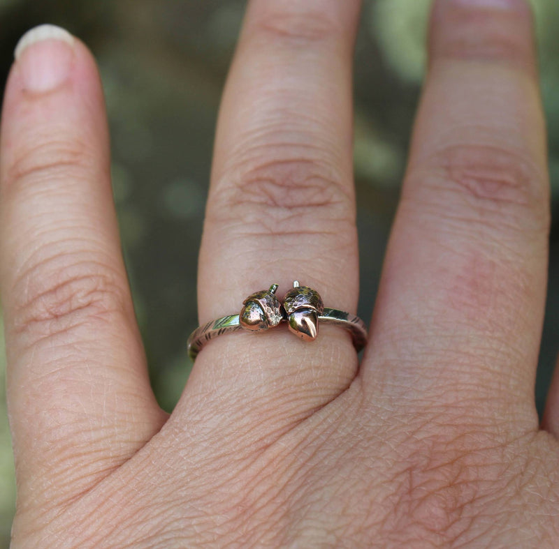 A hand is wearing the copper acorn fall ring to show size.